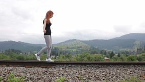 Woman walking on railroad in mountains stock video