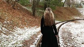 Woman walking on railway tracks. Woman in long black dress and hat walking on railway tracks. Winter. Cold weather. Travel alone. Full HD stock video footage