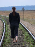 A woman walking on the railwaytrack. A woman in black clothes walking on the railwaytrack stock images