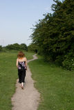 Woman walking with red hair. A woman walking with red hair in a field Stock Photography