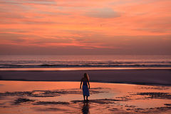 Woman walking, relaxing on the beach at sunrise. Stock Image