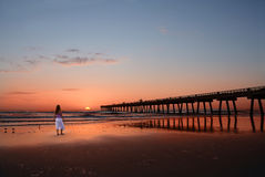 Woman walking, relaxing on the beach at sunrise. Royalty Free Stock Photo
