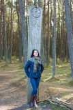 Woman walking and resting in the forest. Brunette woman standing near a tree in the forest stock photo