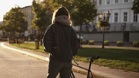 Woman walking beside riding bike on city road. Woman bicycle rider walking on city street. Close up overview shot of stock footage