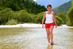 Woman walking in the river Stock Images