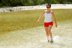 Woman walking in the river Stock Photos