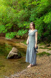 Woman walking on the river bank Stock Photo