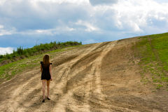 Woman walking on the road Stock Images