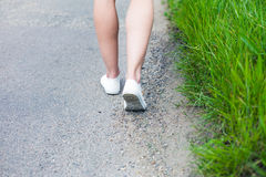 Woman walking on road in the country Stock Photos