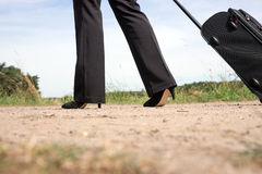 Woman walking on the road with hand luggage suitcase Royalty Free Stock Images