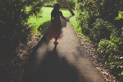 Woman Walking on the Road in the Park Stock Photo