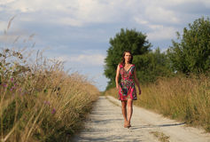 Woman walking on the road Stock Image