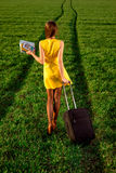 Woman walking on the road with suitcase Stock Images