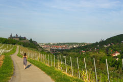 Woman walking on a road with Vineyard landscape view to the castle Marienberg in Wuerzburg Bavaria, Germany Stock Images