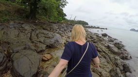 Woman walking on a rocky beach holding hands stock video footage