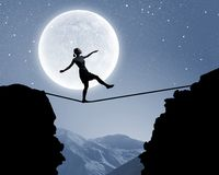 Woman walking on rope. Silhouette of woman balancing on rope above gap Stock Photos