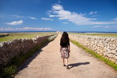 Woman walking rural road to lighthouse Stock Photos