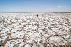 Woman walking in salt dried-up lake Haj Aligholi near Damghan in Iran royalty free stock images