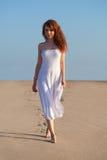 Woman walking on sand Stock Image