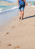 Woman walking on the sand beach Stock Images