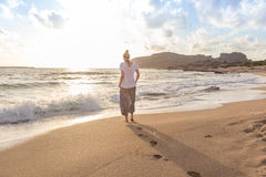 Woman walking on sand beach at golden hour Royalty Free Stock Photo