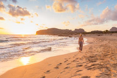 Woman walking on sand beach at golden hour Royalty Free Stock Photos