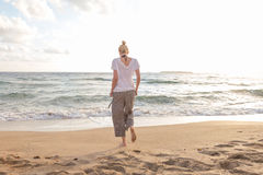Woman walking on sand beach at golden hour. Seashore sunset walk Stock Photography