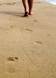Woman walking on sand beach leaving footprints Royalty Free Stock Image