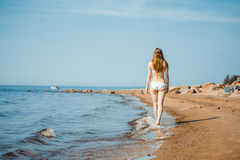 Woman walking on sand beach leaving footprints in the sand. Woman enjoying a walk on the beach Royalty Free Stock Photography
