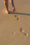 Woman walking on sand beach leaving footprints in the sand. Royalty Free Stock Photo