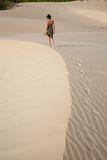 Woman walking at sand curve Stock Photography