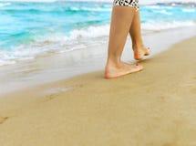 Woman walking through sand Stock Image