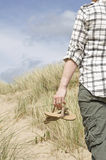 Woman walking in sand dunes holding sandals Stock Image