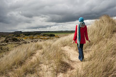 Woman walking in the sand dunes. Picture of a woman walking in the sand dunes Stock Images