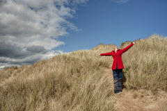 Woman walking in the sand dunes. Picture of a woman walking in the sand dunes Stock Image