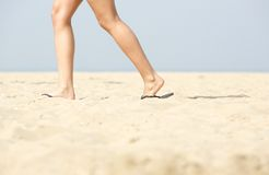 Woman walking in sandals on sand Royalty Free Stock Images