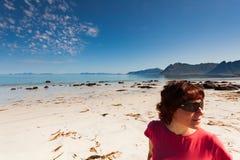 Woman walking on sandy beach, Lofoten Norway royalty free stock photos