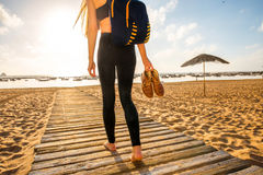 Woman walking on the sandy beach. Young woman in black sport clothes walking with backpack and shoes in the hand on the wooden footpath on the sandy beach Royalty Free Stock Images