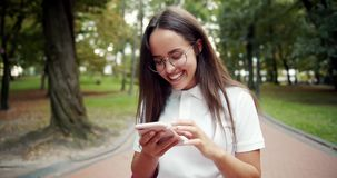 Woman Walking and Scrolling Smartphone stock footage