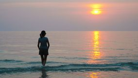 Woman walking on sea coast. At sunset. Relaxing during vacation in Thailand stock video
