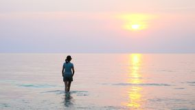 Woman walking on sea coast. At sunset. Relaxing during vacation in Thailand stock video footage