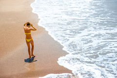 Woman walking on the sea coast Stock Photography