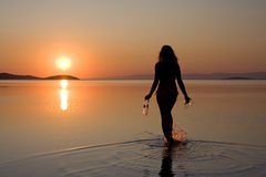 Woman walking in sea at sunset. Rear view of silhouetted woman walking in sea with wine bottle and glasses at sunset Royalty Free Stock Images