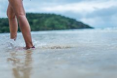 A woman walking in the shallows on the beach Royalty Free Stock Photos