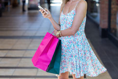 Woman walking with shopping bags and holding smartphone Stock Photos