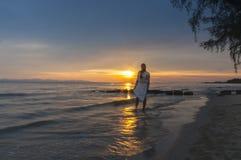 Woman walking at shore alone Stock Photo
