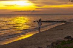 Woman walking at shore alone Stock Image
