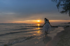 Woman walking at shore alone. On sunset royalty free stock image