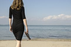 Woman walking on the shore of the beach towards the sea. Rear view of woman in black tight dress walking on the shore of the beach towards the sea stock image