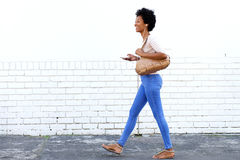 Woman walking on sidewalk with headphones and smart phone Royalty Free Stock Photo